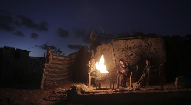 A Palestinian family warm themselves up with a fire outside their makeshift house during a power cut in Khan Younis in the southern Gaza Strip (Khalil Hamra/AP)