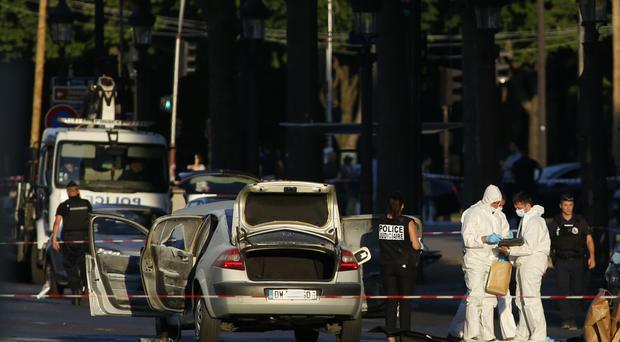 Officers at the scene in the Champs-Elysees in Paris after a man rammed a car carrying explosives into a police vehicle (AP Photo/Matthieu Alexandre)