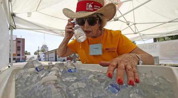 Salvation Army volunteer Jackie Rifkin tries to keep cool at she works at a hydration station (AP)