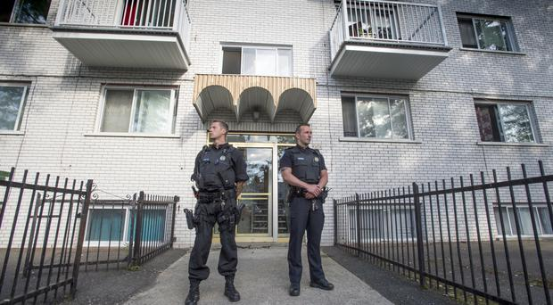 Police stand guard in front of an apartment building in Montreal (AP)