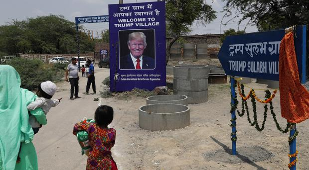 A photograph of US President Donald Trump is displayed at the entrance of Trump Sulabh Village in Maroda, India (Tsering Topgyal/AP)