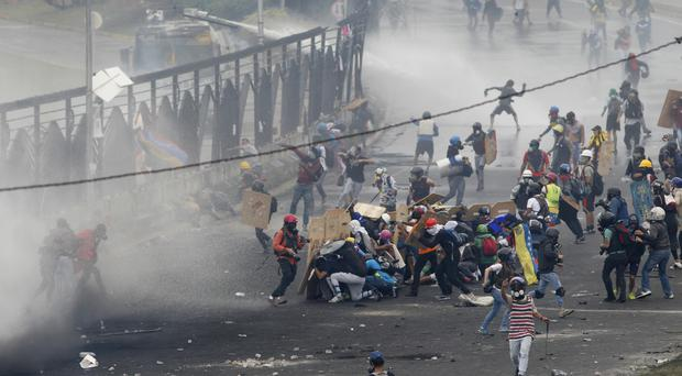 Demonstrators clash with authorities at the fence of La Carlota Air Base in Caracas
