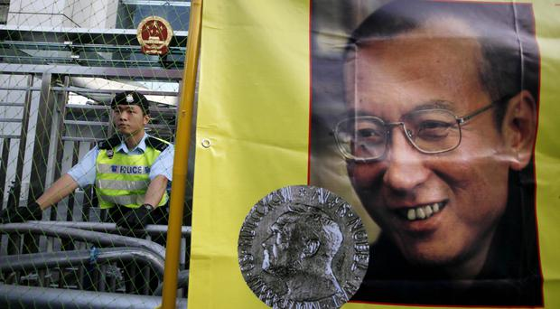 A police officer stands guard beside a picture of jailed Chinese dissident Liu Xiaobo