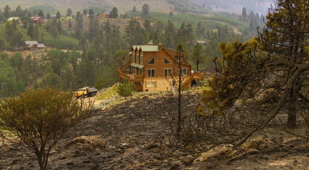A home near a burnt hillside caused by a wildfire fire on the west side of Panguitch Lake in Utah (Jordan Allred/The Spectrum via AP)
