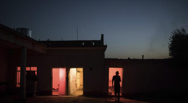 An Iraqi special forces soldier walks out of his room at a temporary base in a village near Mosul, Iraq (AP)