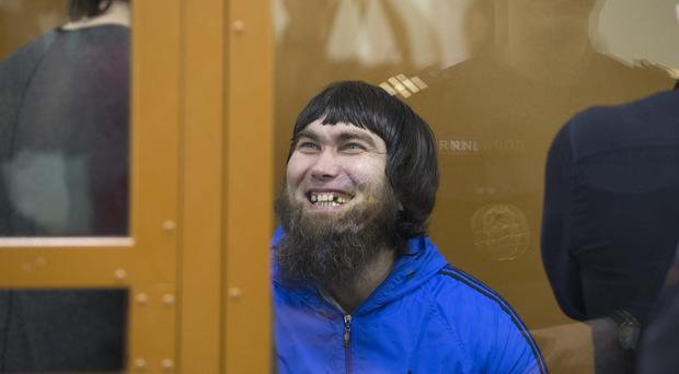 Anzor Gubashev, one of five defendants found guilty of involvement in the killing of Boris Nemtsov, smiles in a glass enclosure in a Moscow military district court (AP)