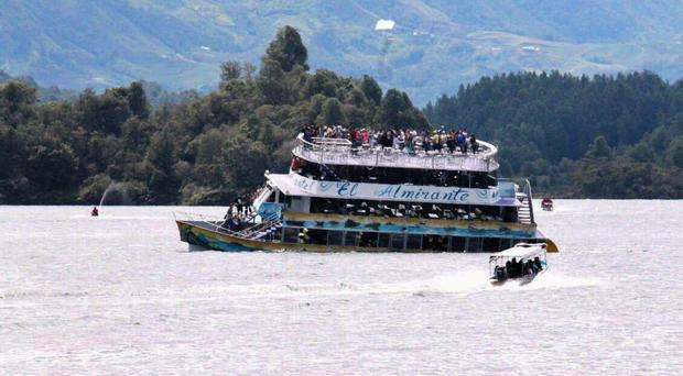 A boat races towards the sinking El Almirante ferry at a reservoir in Guatape, Colombia (Juan Quiroz via AP)