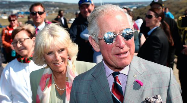 The Prince of Wales and the Duchess of Cornwall try on snow glasses made by a local as they tour the Sylvia Grinnell Territorial Park in Canada