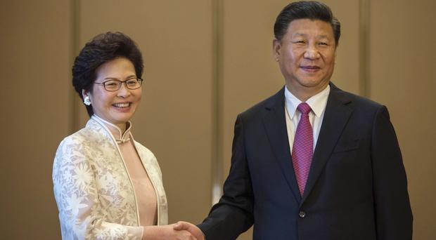 China's President Xi Jinping poses with Hong Kong's chief executive Carrie Lam, but the smiles were followed by a stern warning (Pool Photo/AP)