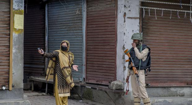 A Kashmiri woman asks an Indian paramilitary soldier to let her pass before being turned back during a curfew in downtown area of Srinagar (AP)
