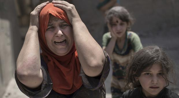 A woman screams while fleeing with her family through a destroyed alley in Mosul's Old City (Felipe Dana/AP)