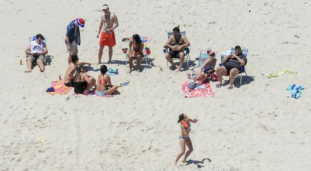 Chris Christie, right, uses the beach with his family and friends (AP)