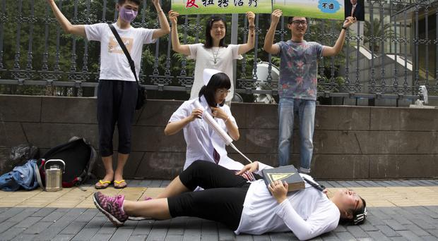 Gay rights campaigners act out electric shock treatment to protest outside the court in Beijing, China (AP)