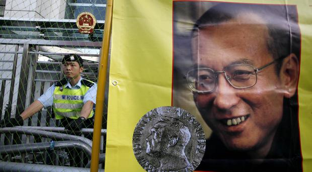 A police officer stands guard beside a picture of Liu Xiaobo outside the Chinese government liaison office in Hong Kong, in 2010 (AP Photo/Kin Cheung, File)