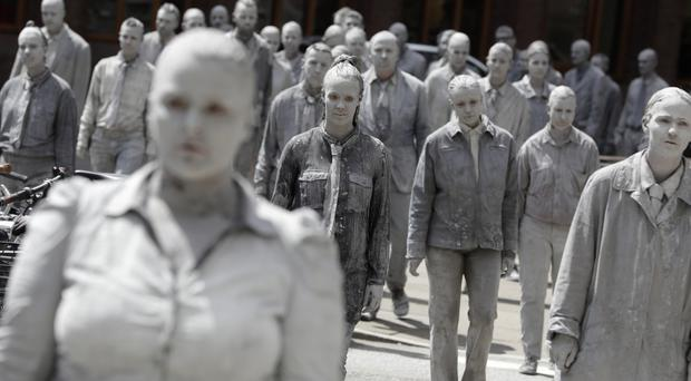 Hundreds of people painted like clay figures move slowly and silently through Hamburg to protest against the G20 summit (AP)
