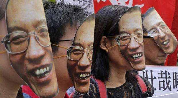 Protesters wear masks of jailed Chinese Nobel Peace laureate Liu Xiaobo (AP Photo/Vincent Yu, File)
