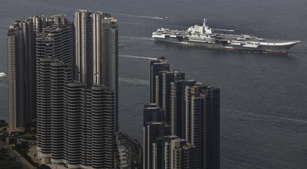 The Liaoning, China's first aircraft carrier, sails into Hong Kong for a port call (AP Photo/Vincent Yu)