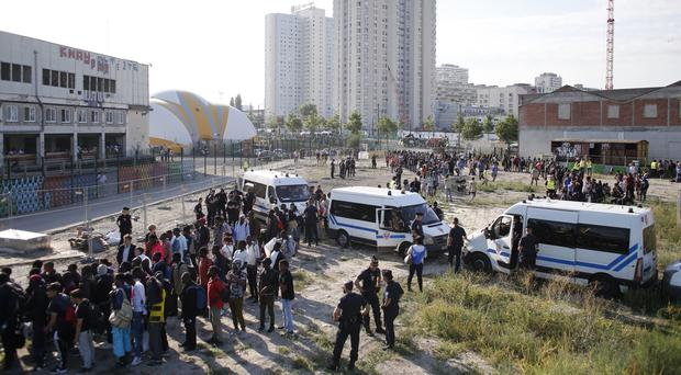 Migrants gather to be taken away from a makeshift street camp in Paris (AP)