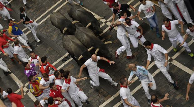 Revellers run during the second running of the bulls at the San Fermin Festival in Pamplona, northern Spain (AP/Alvaro Barrientos)