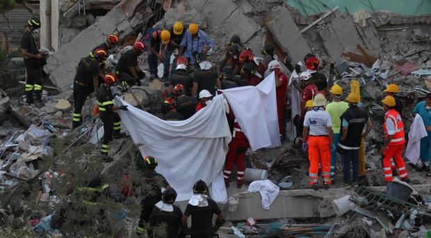 Rescuers work in the rubble of a building that collapsed in Torre Annunziata, near Naples, southern Italy (Ciro Fusco/Ansa via AP)