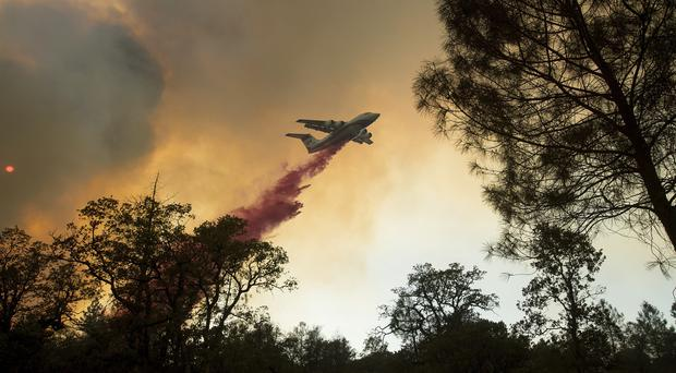 A plane drops retardant while fighting a wildfire near Oroville, California (AP Photo/Noah Berger)