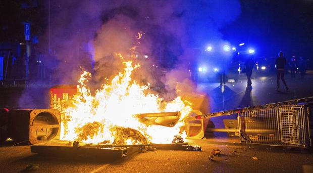 Policemen stand behind a burning barricade in Hamburg (Daniel Bockwoldt/dpa via AP)