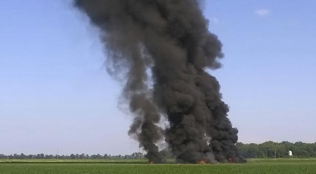 Smoke and flames rise into the air after a military transport airplane crashed in a field near Itta Bena, (Jimmy Taylor via AP)