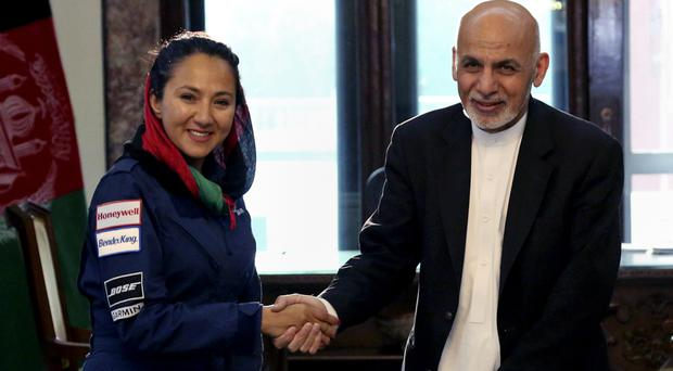Afghan President Ashraf Ghani shakes hands with Afghan-American female pilot Shaesta Waiz at the Presidential Palace in Kabul (Afghan Presidential Palace via AP)