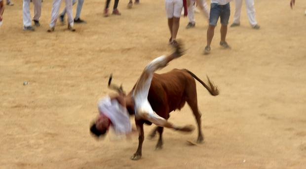A man is pushed by a bull on the last day of the San Fermin Festival in Pamplona, northern Spain (AP Photo/Alvaro Barrientos)