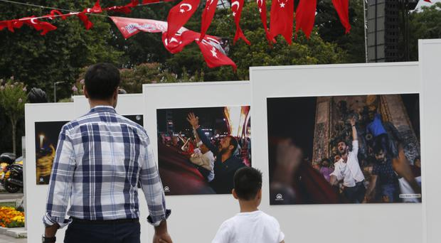 People visit an outdoor photo exhibition, featuring photographs of the July 15 2016 coup attempt, in Istanbul (AP)