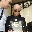 Liu Xia, wife of Nobel Peace Prize winner Liu Xiaobo, holds a portrait of him during his funeral (Shenyang Municipal Information Office/AP)