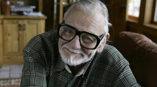 Director and writer George Romero poses has died at the age of 77 (AP)