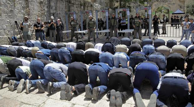 Israeli border police officers stand guard as Muslim men pray outside the Al Aqsa Mosque compound, in Jerusalem (AP)