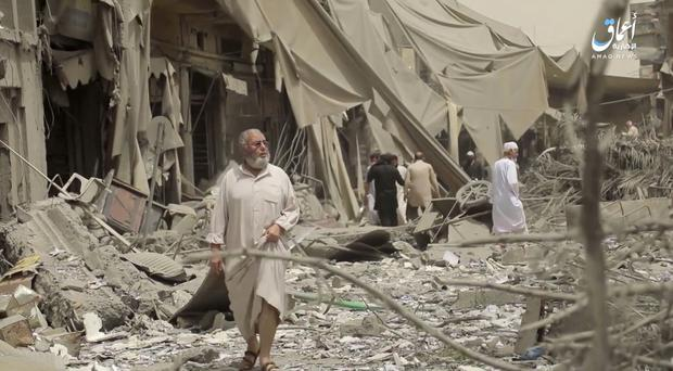 A video grab posted by the Aamaq News Agency, a media arm of the Islamic State group, shows people inspecting damage from air strikes and artillery shelling in Raqqa (Aamaq News Agency via AP)