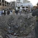 Security forces stand next to a crater created by a massive explosion in Kabul, Afghanistan (AP/Rahmat Gul)