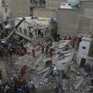 Volunteers look for trapped people at the site of a building collapse in Karachi, Pakistan (AP Photo/Shakil Adil)
