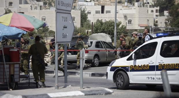 Soldiers at the scene of the attack near Hebron (AP)