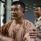Lt Gen Manas Kongpaen is escorted by a Thai correction officer on his arrival at the Criminal Court in Bangkok. (AP)