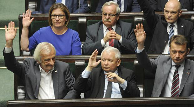 Polish politicians from the ruling Law and Justice party approve a law on court control in Warsaw. (AP)