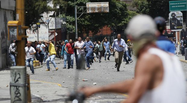 Pro-government supporters confront anti-government protesters in Caracas, Venezuela (Ariana Cubillos/AP)