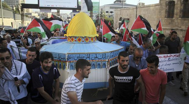 Palestinians carry a model of the Al Aqsa Mosque compound during a protest against the metal detectors placed at the entrance (AP Photo/Mahmoud Illean)