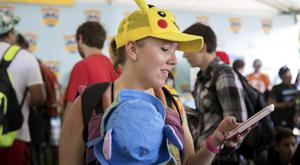 Lauren Schuster of Miami looks at her phone as she struggles to get Pokemon Go working in Chicago (Erin Hooley/Chicago Tribune via AP)
