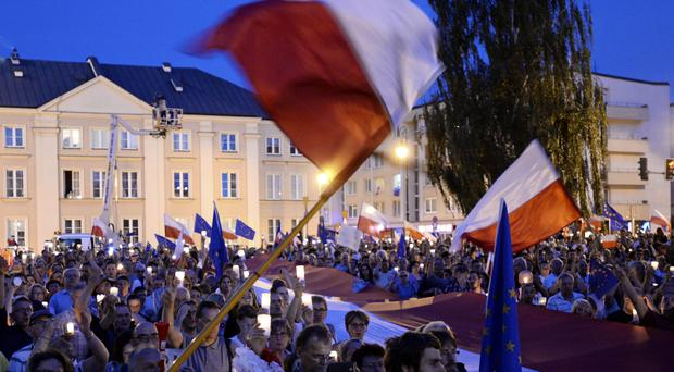 Anti-government protesters raise candles and wave flags as they gather in front of the Supreme Court in Warsaw, Poland (AP)