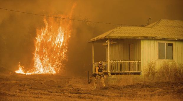 Flames rise behind a vacant house as a firefighter works to halt a wildfire near Mariposa, California (AP)