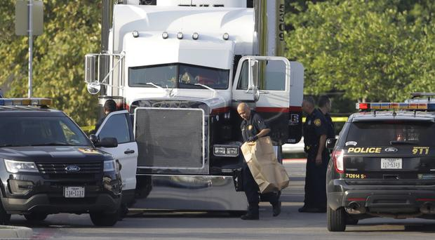 San Antonio police officers investigate at the scene where nine people were found dead in a tractor-trailer (AP Photo/Eric Gay)