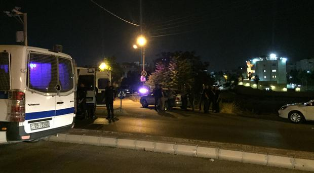 Security officials near the Israeli embassy in Amman after a shooting that left two men dead and one injured