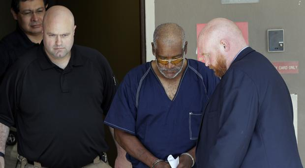 James Mathew Bradley Jr, 60, of Clearwater, Florida, centre, is escorted out of the federal courthouse following a hearing in San Antonio (AP)