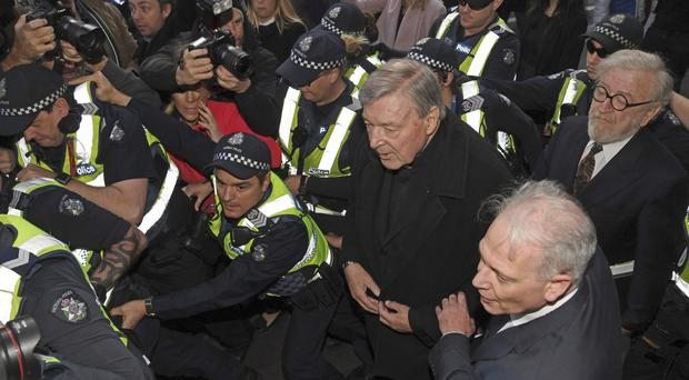 Cardinal George Pell, surrounded by police, arrives at Melbourne Magistrates Court (AAP Image/AP)