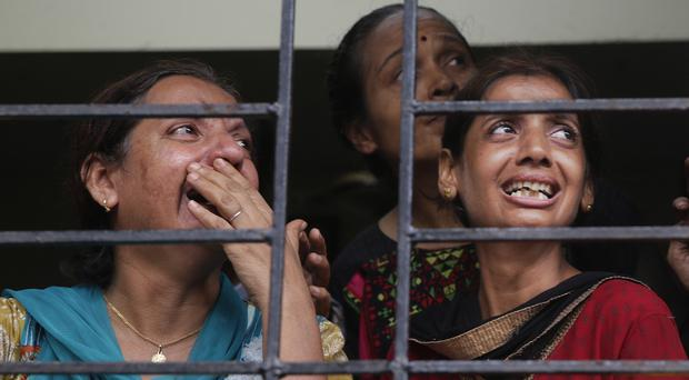 Relatives of people trapped under the rubble watch the rescue operation in Mumbai (AP)