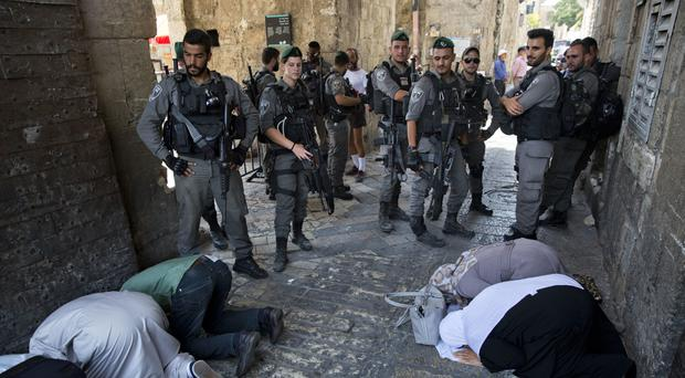 Palestinians pray as Israeli border police officers stand guard at the Lion's Gate in Jerusalem's Old City (AP/Oded Balilty)